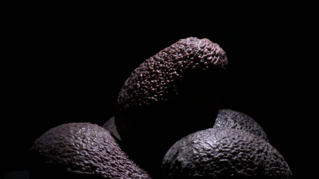 Mountain of ripe hass avocados fruit at black background